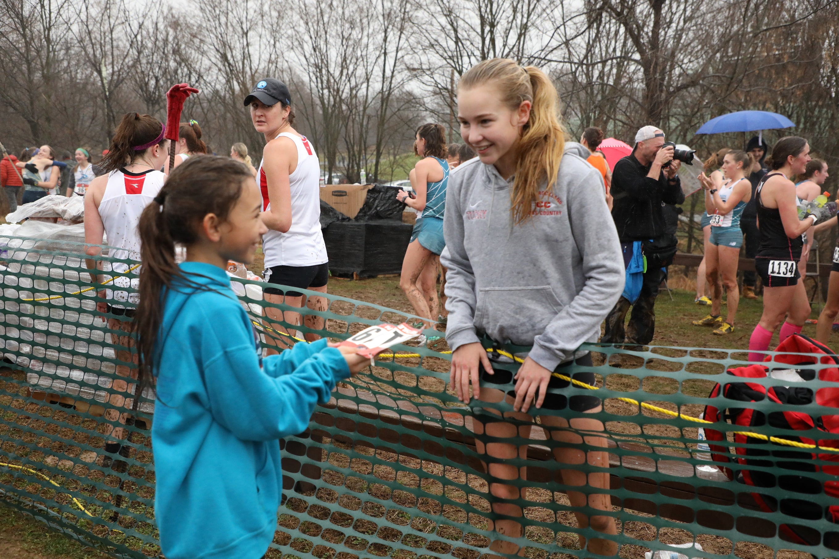 Katelyn Tuohy, 17, greets 10-year-old Paige Stoltz of Hershey, Pennsylvania. Tuohy, a high school senior, won the Nike Cross Nationals meet for the third time a week before racing the 2019 USATF Club Cross Country Championships, where she placed second in her first competition against pro runners.
