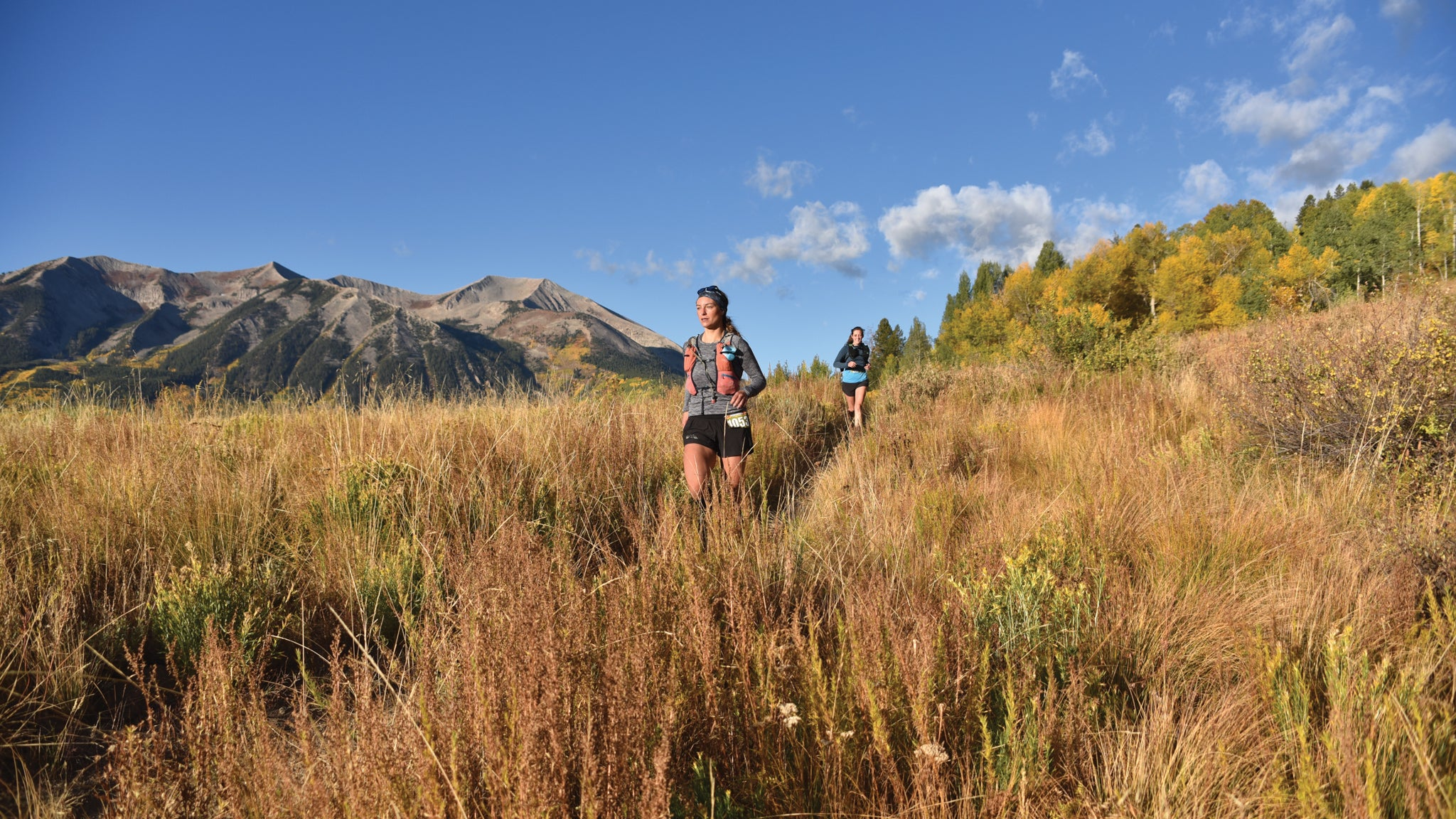 Women run through a mountain meadow during the Crested Butte Ultra