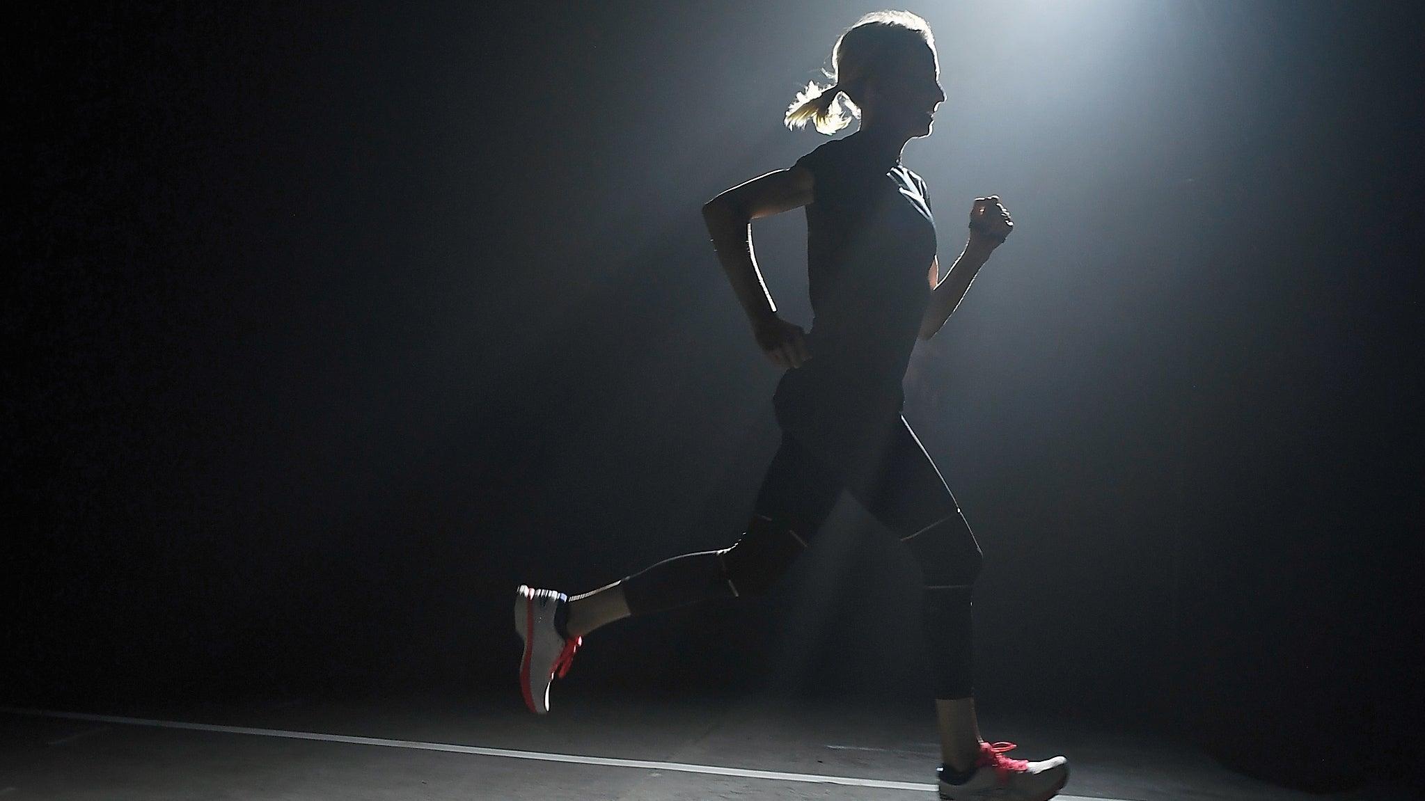 Deena Kastor running on a darkly lit indoor track