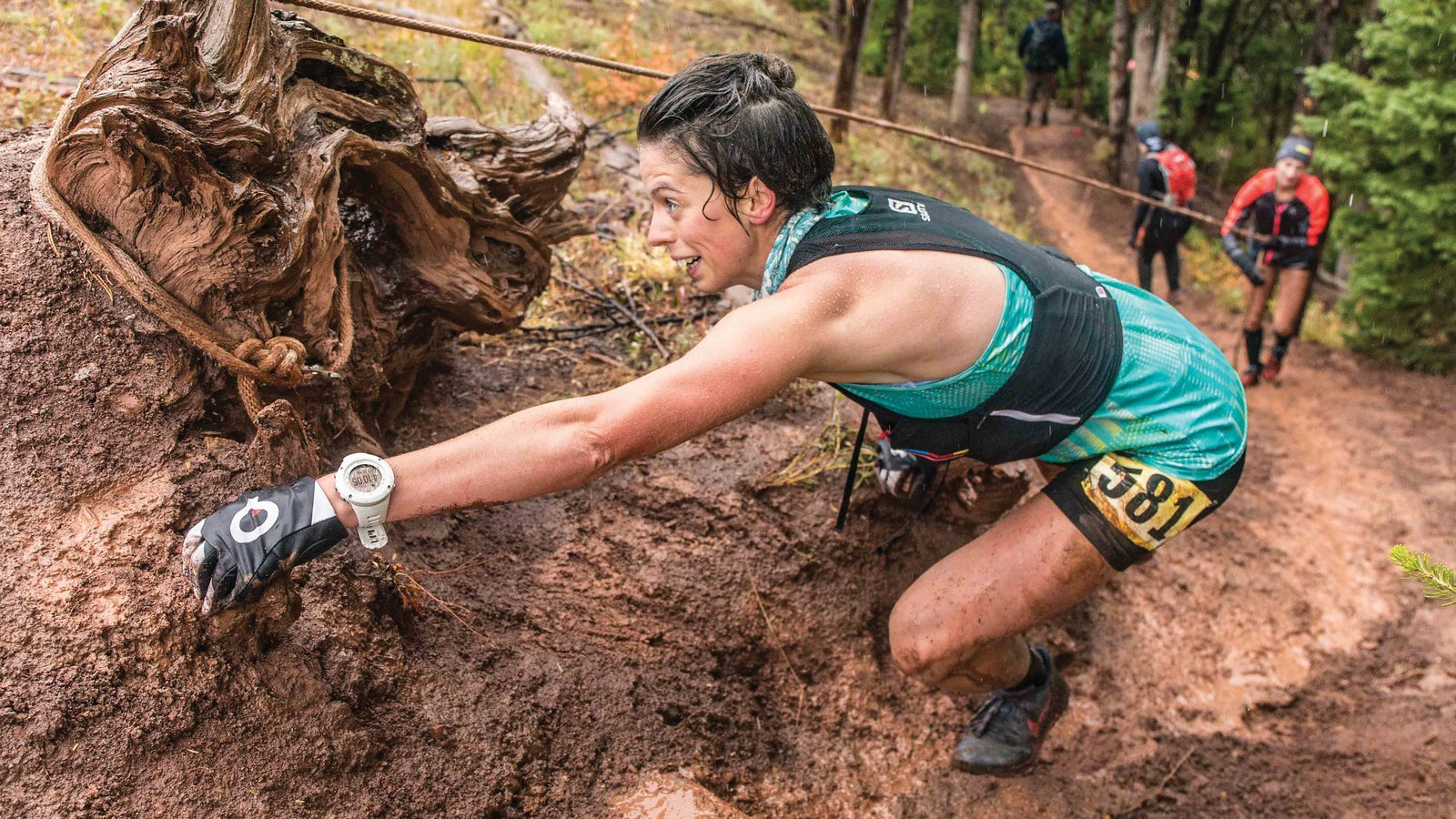 A woman climbs up a muddy slope during Run the Rut