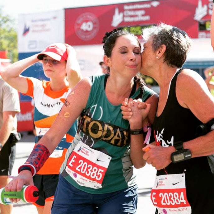 Kelly Herron and her mom kiss at the finish line of a race