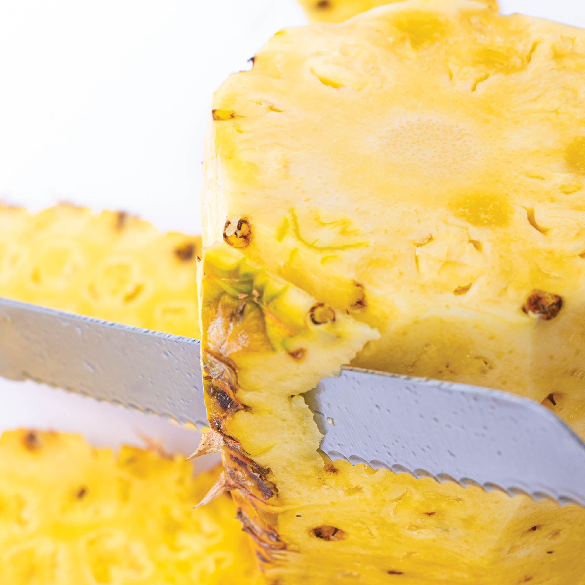 Cutting rind off pineapple