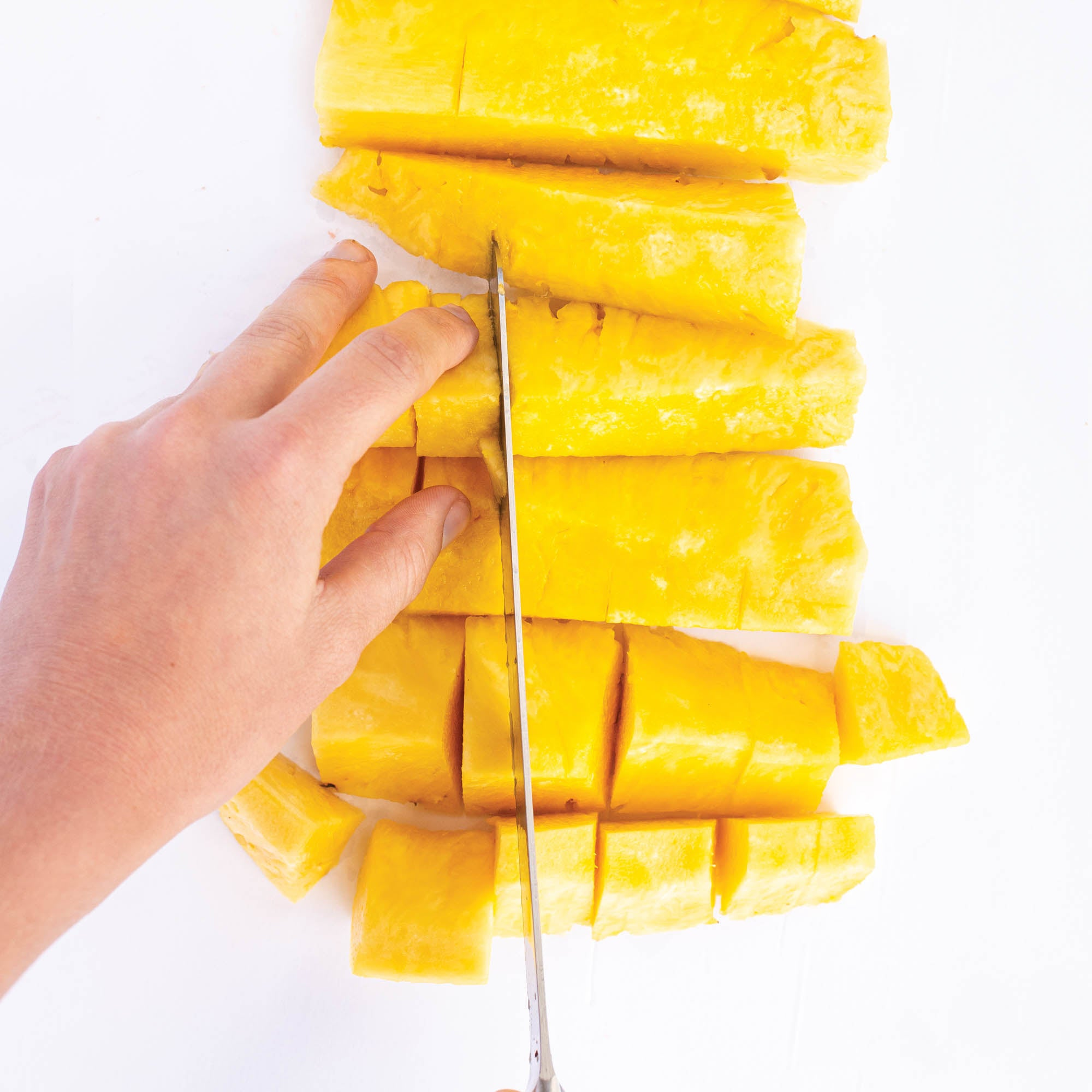 Slicing pineapple into bite-sized pieces