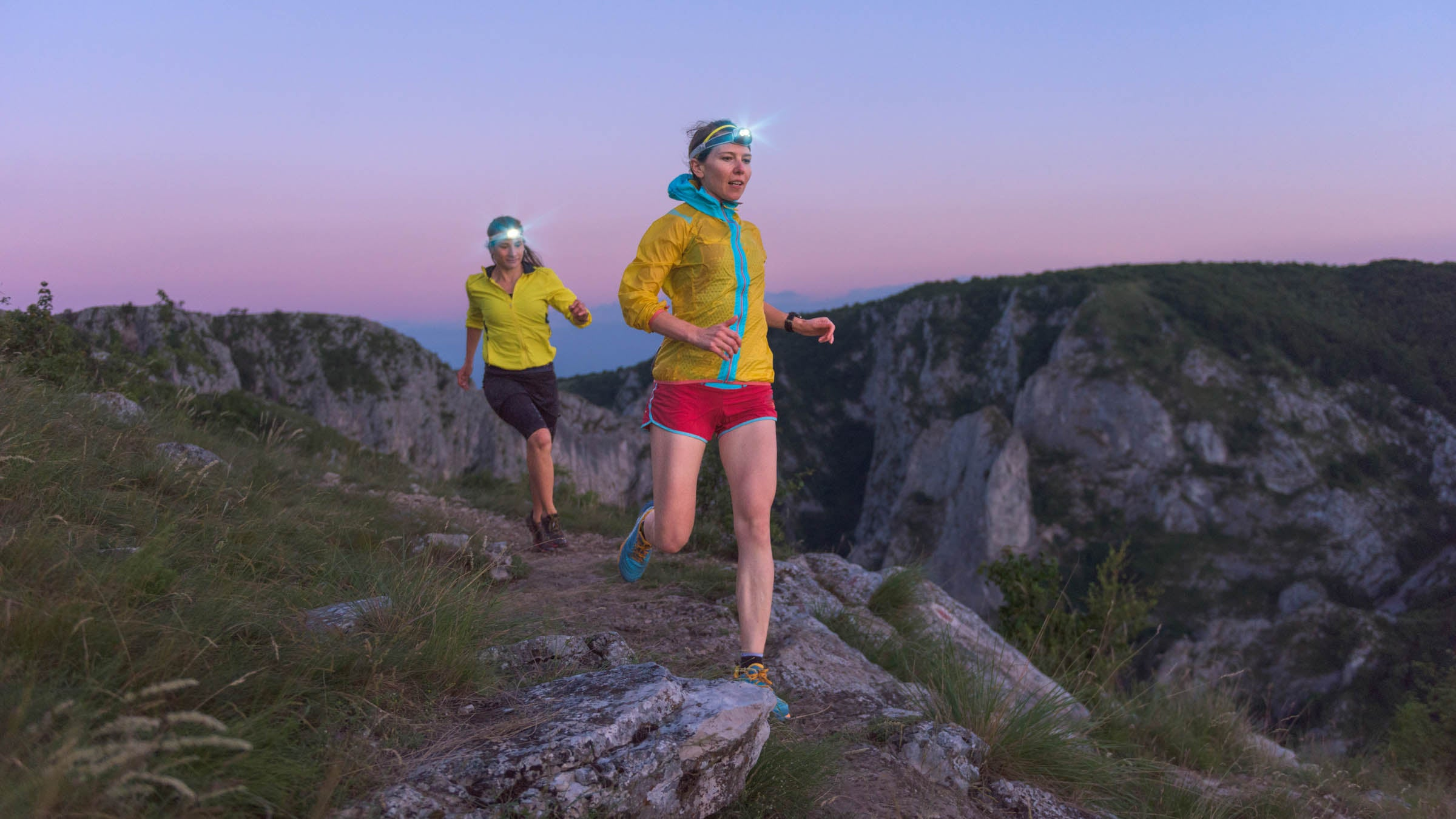 Two female athletes wearing headlamps and running along a hill at sunset