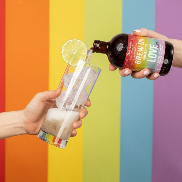 brew dr kombucha being poured into a glass in front of rainbow background
