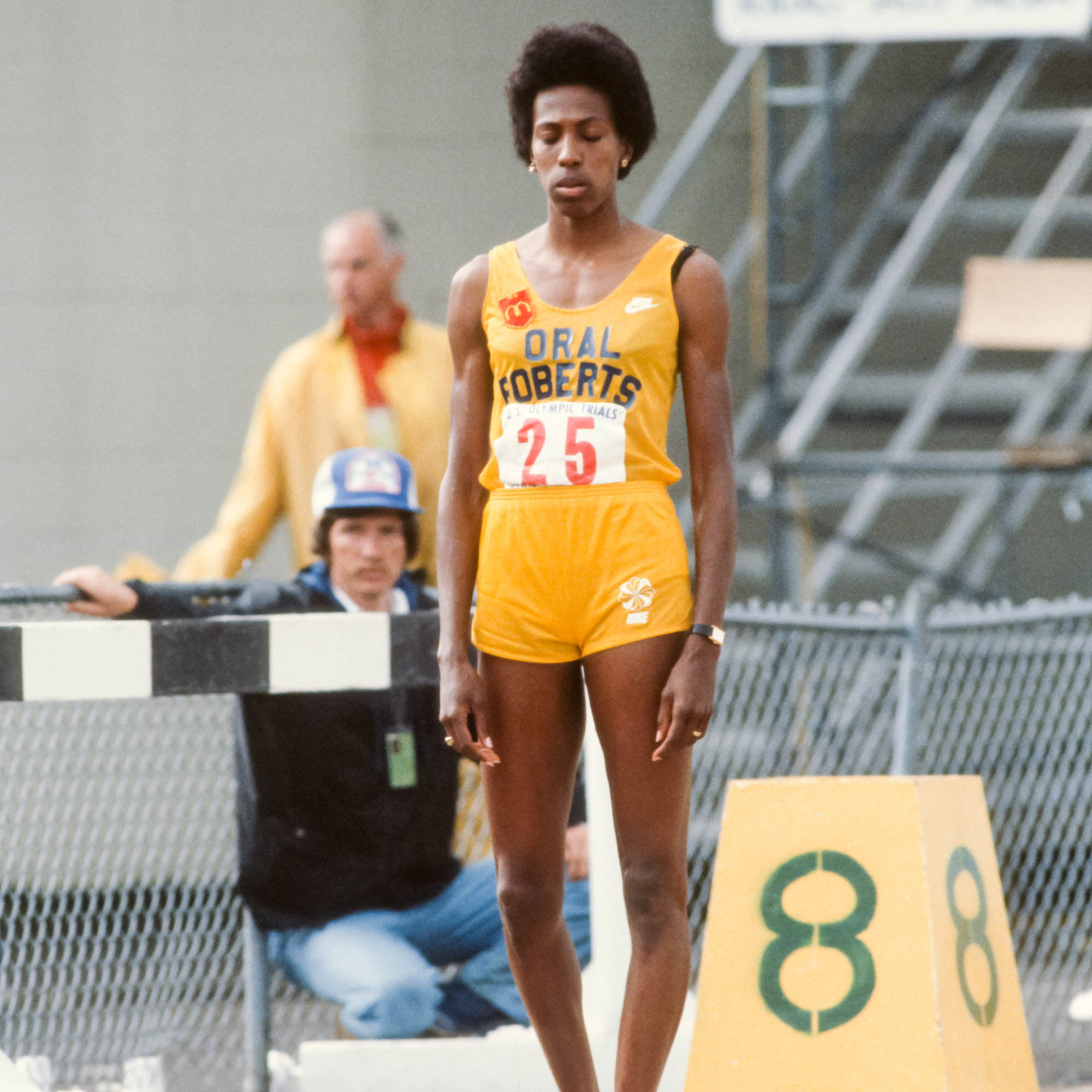 A tall woman in yellow stands alone on a wet track