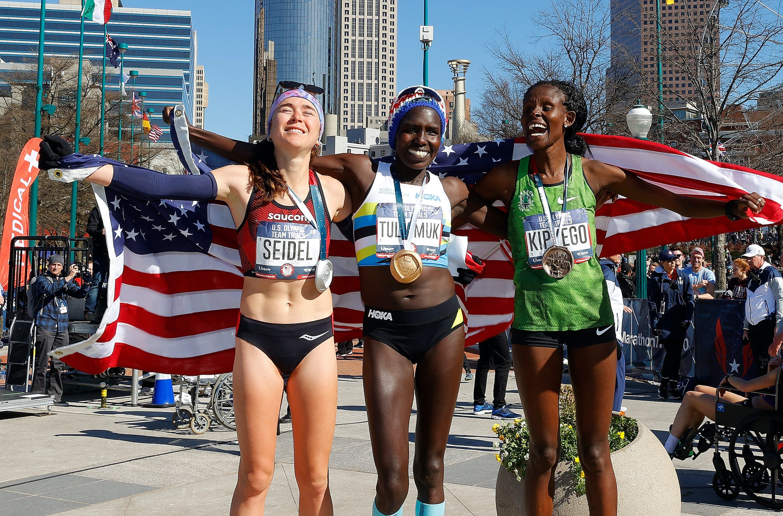 Molly Seidel, Aliphine Tuliamuk, and Sally Kipyego pose after finishing in the top three of the Women's U.S. Olympic marathon team trials on February 29, 2020 in Atlanta, Georgia.